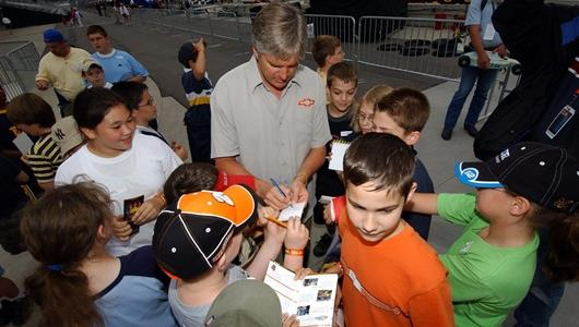 Young fans get autographs from 1998 Indy 500 winner Eddie Cheever on Community Day at the Indianapolis Motor Speedway.