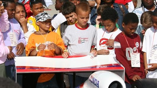 School kids get up close and personal with an IndyCar at the Indianapolis Motor Speedway.