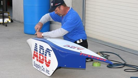 A crew member works on the side pod of the Number 14 car in the paddock of the Indianapolis Motor Speedway.