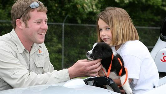 A young girl holds a puppy from Best Friends Animal Society.