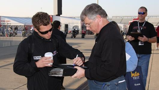 Ryan Briscoe signs an autograph for a fan on the morning of Pole Day qualifying.