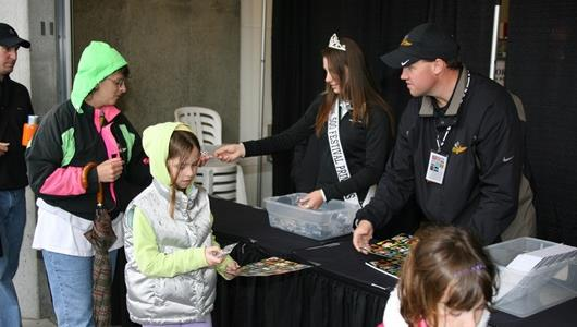 A 500 Princess hands out collector pins to race fans on day two of qualifications.