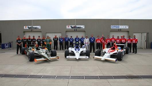 #99 Townsend Bell, #15 Buddy Rice, #23 Milka Duno and their crews lined up for a picture in front of the garages at Indianapolis Motor Speedway.