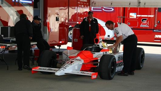 Team Penske removes Helio Castroneves' car from the trailer during rookie orientation.