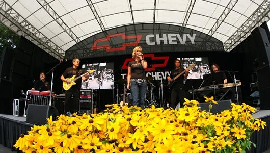 Fans enjoy live music from the Chevy Stage on Chevy Day at the Brickyard.