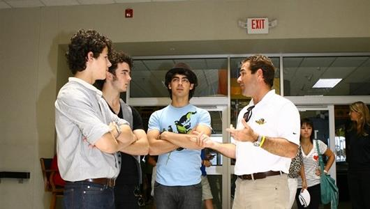 Nick (left), Kevin (center left) and Joe Jonas (center right) listen to a tour of the IMS Hall of Fame Museum from IMS President and COO Joie Chitwood.