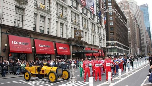 The starting field for the 2009 Indianapolis 500 poses in Herald Square in New York, adjacent to Macy's, with the Marmon Wasp driven to victory in the 1911 Indianapolis 500 by Ray Harroun and the Borg-Warner Trophy.