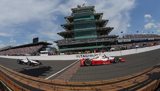 Juan Pablo Montoya crosses the Yard of Bricks with his fist raised as celebrates winning the 99th Running of the Indianapolis 500 Mile Race by .1046 to beat teammate Will Power