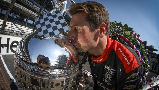 Will Power kisses the Borg-Warner Trophy on the Yard of Bricks during his winner's photo shoot at the Indianapolis Motor Speedway