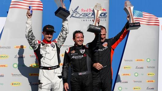 Second place Pete McLeod, first place Michael Goulian and third place Nicolas Ivanoff celebrating on victory podium.