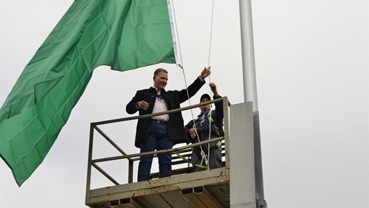Jim Cornelison beginning to raise the green flag to symbolize the start of the 2019 IndyCar season.
