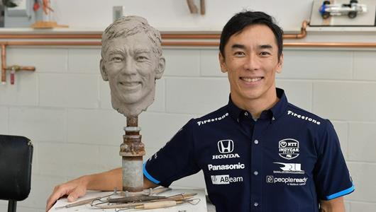 Takuma Sato poses next to his clay sculpture that will signify his historic win in the 2020 Indianapolis 500 presented by Gainbridge. Photo by Scott LePage, BorgWarner.